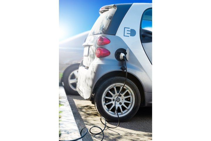 Electric car charging at station with power cable plugged In