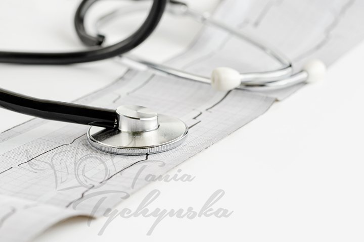 Stethoscope and cardiogram on white background.