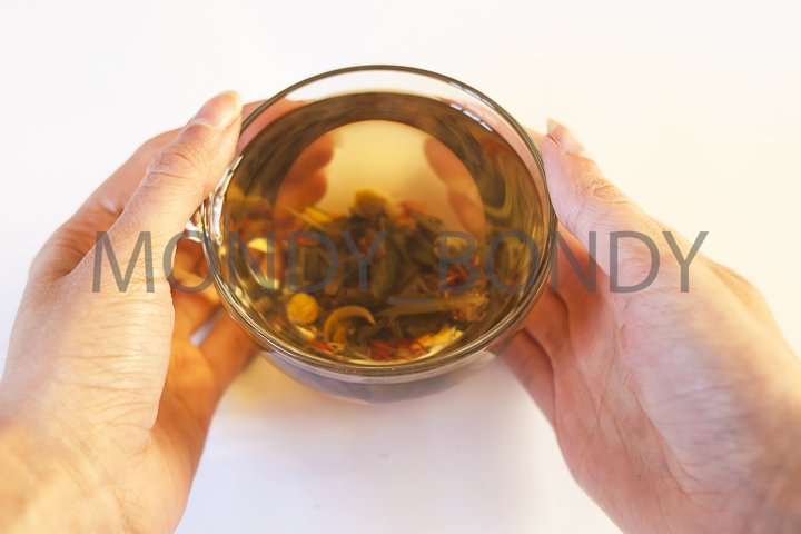 A transparent cup of herbal tea in the hands