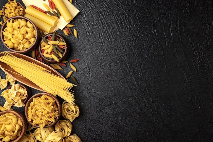Different pasta types on black background with copy space