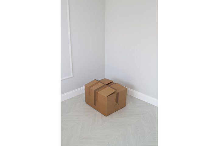 shabby cardboard box in the corner in an empty new room