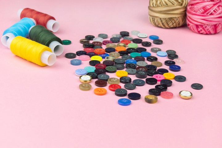 Multicolored threads and buttons on a pink background.
