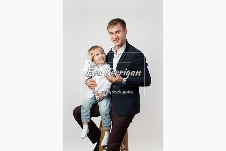 A cboy of 3 years old is sitting in the arms of his father.