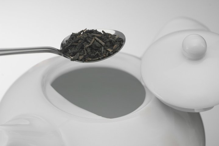 Spoon with tea leaves and a white ceramic teapot, close-up