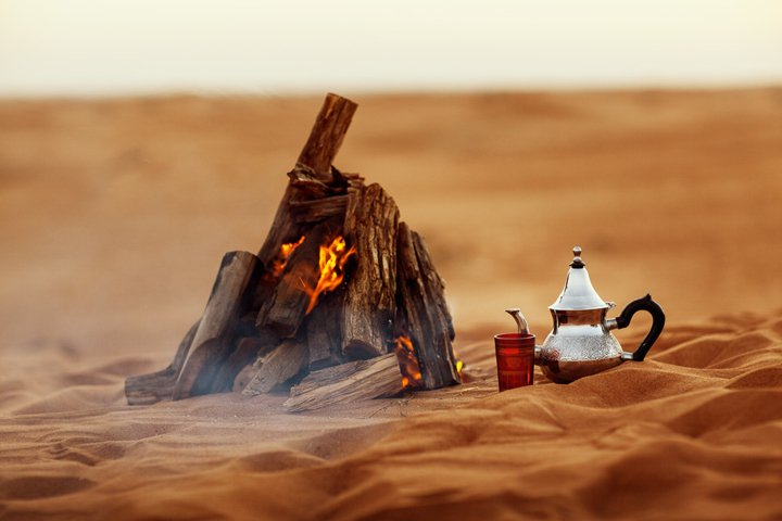 Dates, teapot, cup with tea by the bonfire in the desert