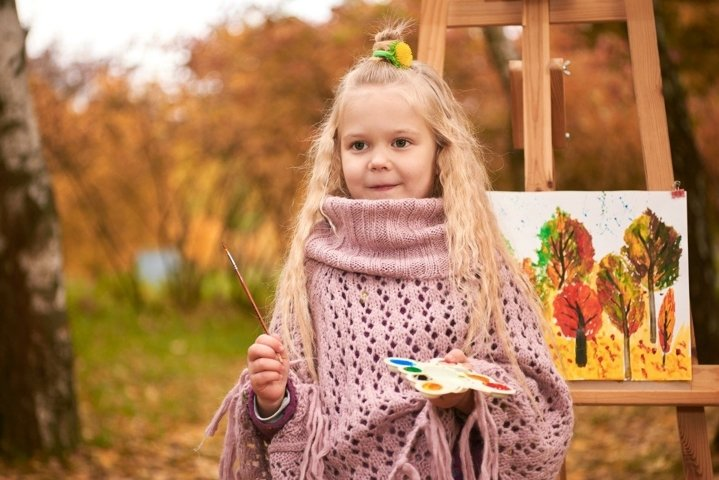 portrait of cute little girl artist. child in autumn draws