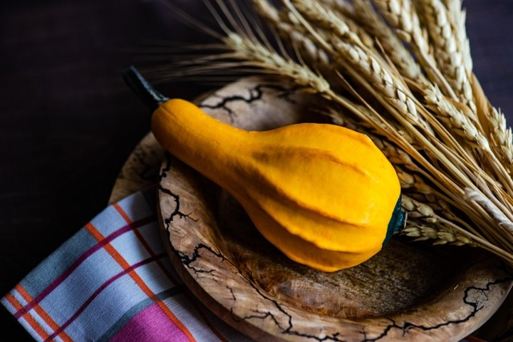 Autumnal table setting with bright yellow leaves and pumpkin