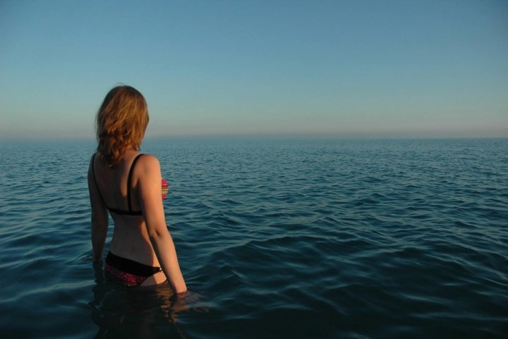 A girl stands in the sea at sunset