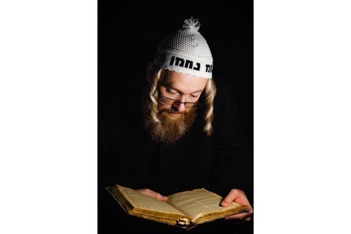 Hasidic jew reading Torah. Orthodox jew praying in the dark