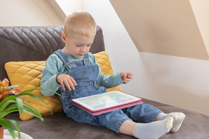 Cute toddler boy holding digital tablet and watching cartoon