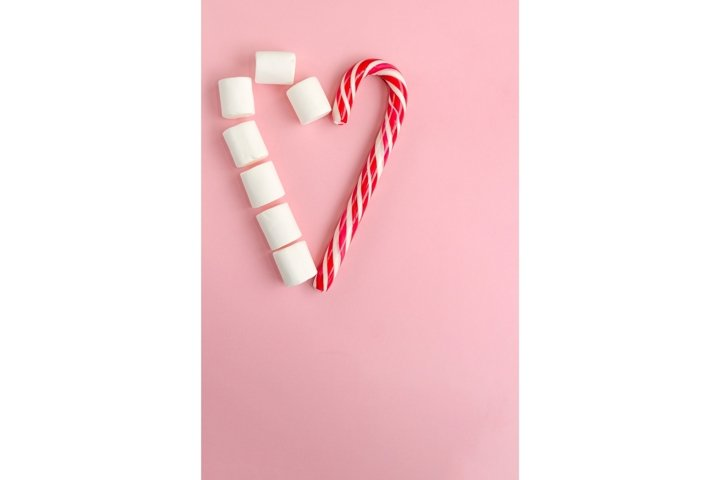 Heart shape made of candy cane and white marshmallows