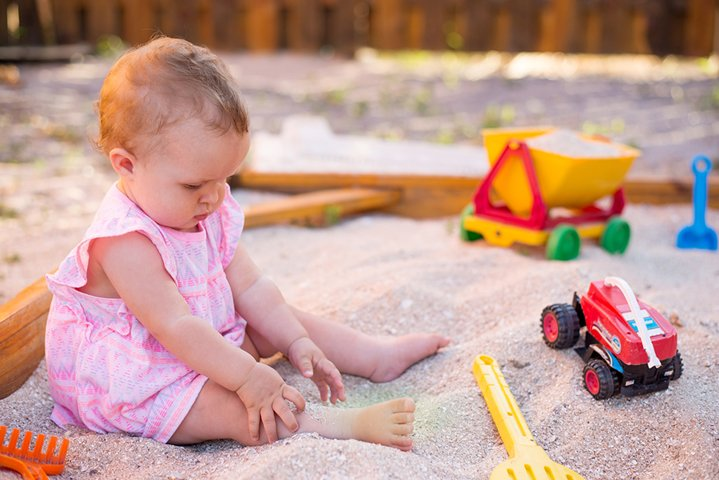 baby girl playing in sandbox on outdoor playground