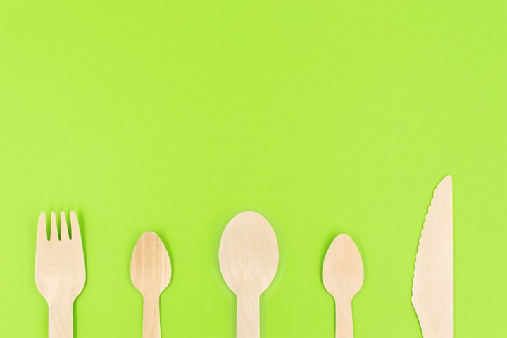 Eco friendly disposable cutlery on green background