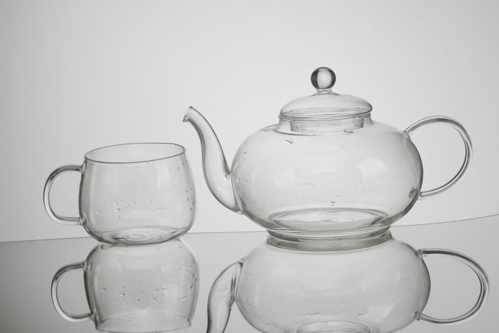 Transparent glass teapot and tea cup with reflection