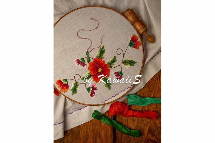 Flower embroidery on white textile in hoop wooden background
