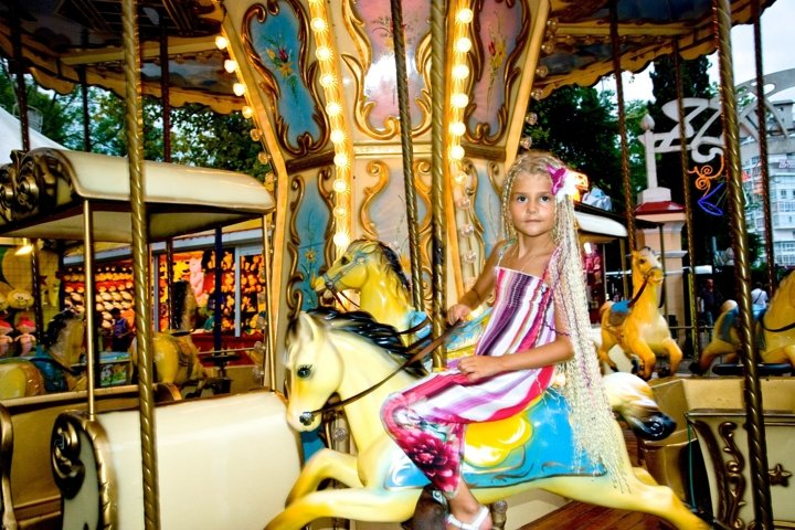 The litlle girl rides a carousel.