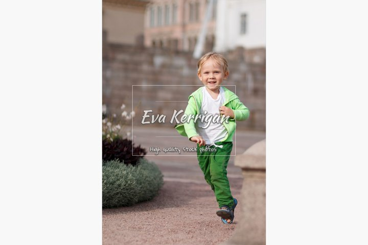 A blond child of European appearance in green clothes.