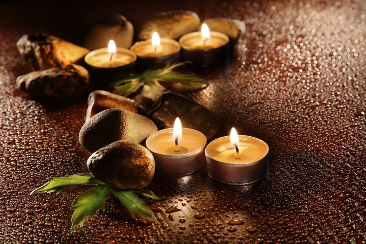 Burning candles and drops of water. Stone therapy.