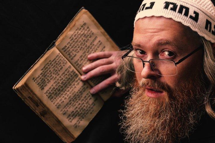 Red bearded Hasidic Jew with sidelocks reading Torah