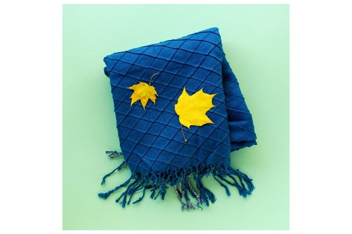 Blue scarf with maple leaves on a mint background