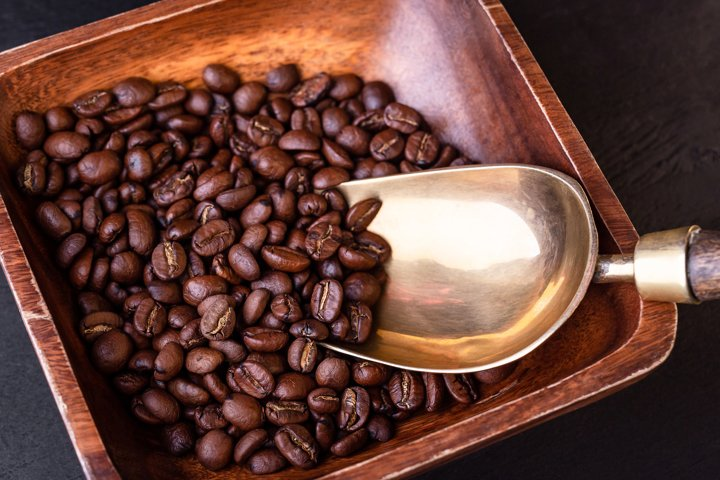 Coffee theme. Plate with coffee beans on black wooden table.