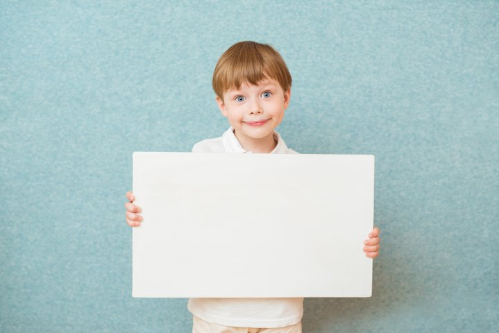 Young boy holding white blank board on blue background