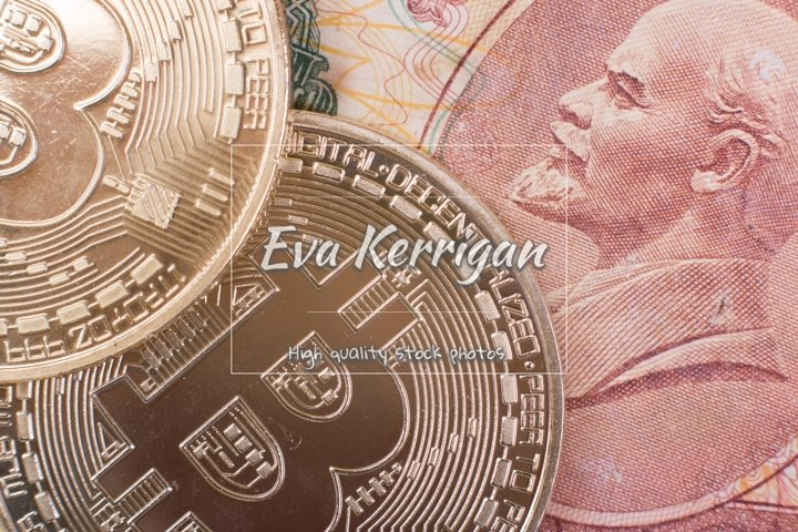 Two Bitcoin coins lie on top of Soviet paper money rubles.