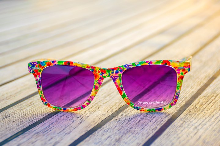 Luxurious purple glasses lie on the deck of the yacht