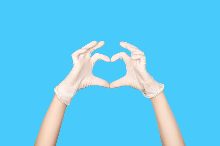 Hand in a white latex glove showing Heart sign
