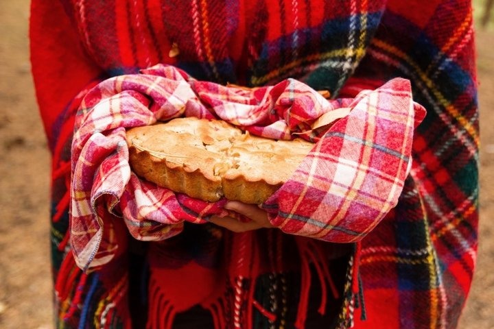 Woman in red Scottish plaid is holding apple pie.