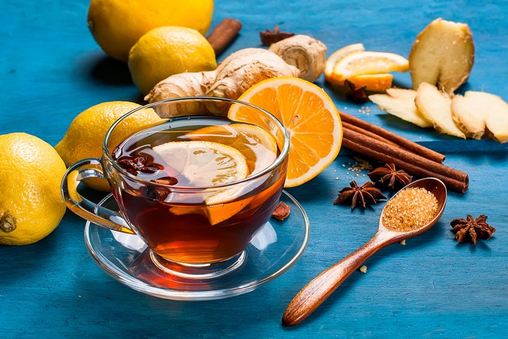 Cup of Ginger tea with lemon and honey on dark brown wooden