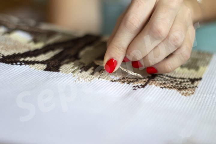 Woman sewing cross-stitch and enjoying her hobby
