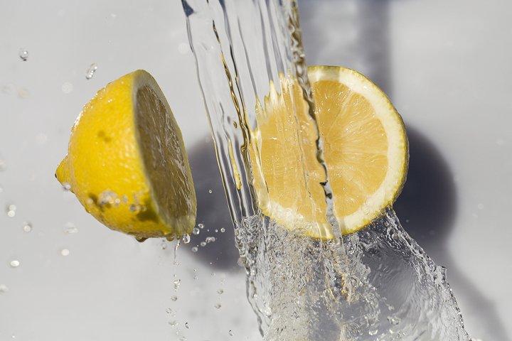 Fresh lemon and water splash on white background. summer con
