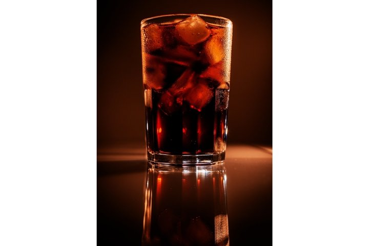 Glass of cola with ice on brown background with reflection