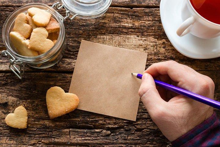 homemade cookies, a mug, a man writes a note