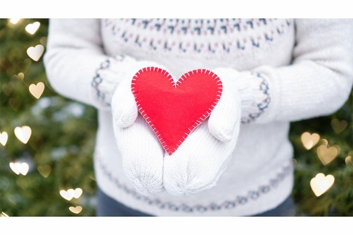 Red heart in the hands of a girl in heart shaped bokeh