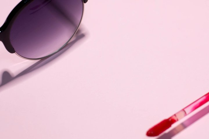 Sunglasses and red lipstick on a pink background