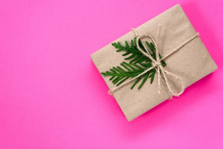 Gift box wrapped in kraft paper tied with twine on pink