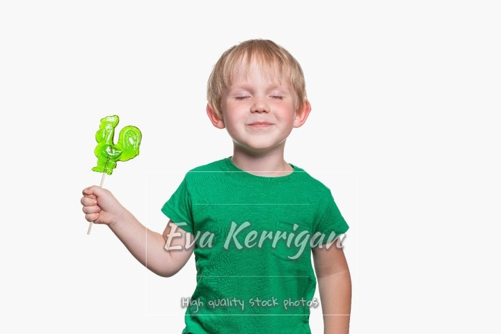 Child boy 4 years old in a green T-shirt holds a lollipop.