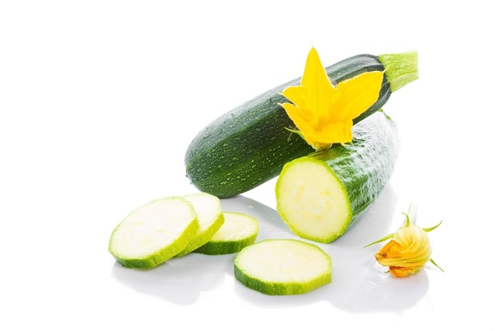 Zucchini or green marrow squash with green leaves and flower