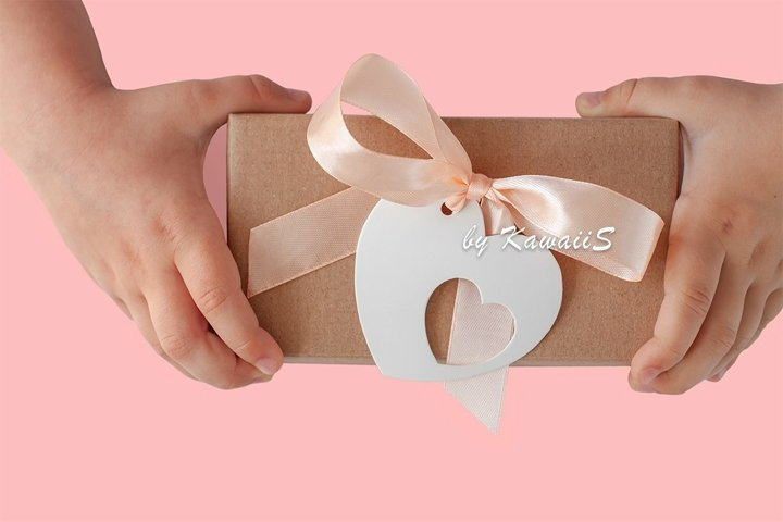 Childs hands holds gift box with heart card tag ribbon bow