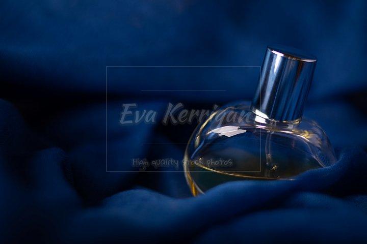 Glass bottle of perfume on dark blue mysterious romantic.