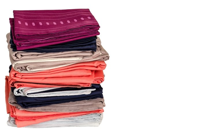 Stack of folded clean bed linens on white background