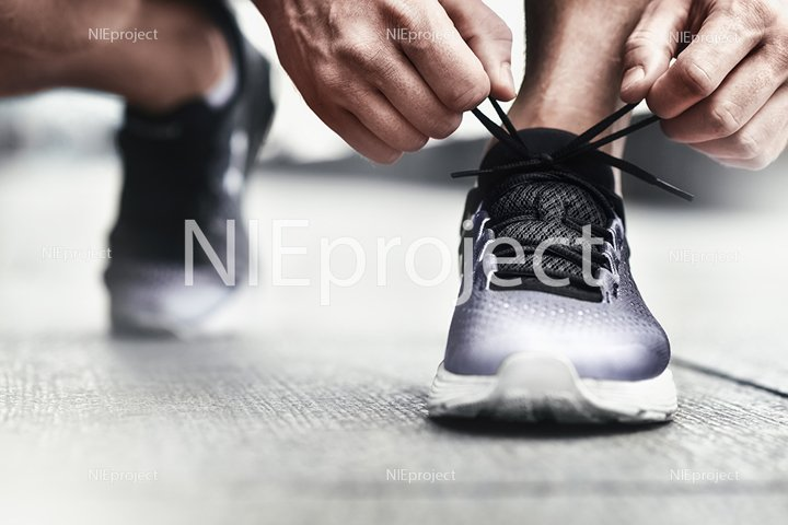athlete tying his shoelaces at sports sneakers