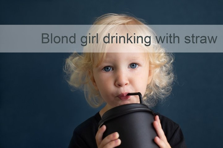 Blond toddler girl drinking from reusable cup using straw