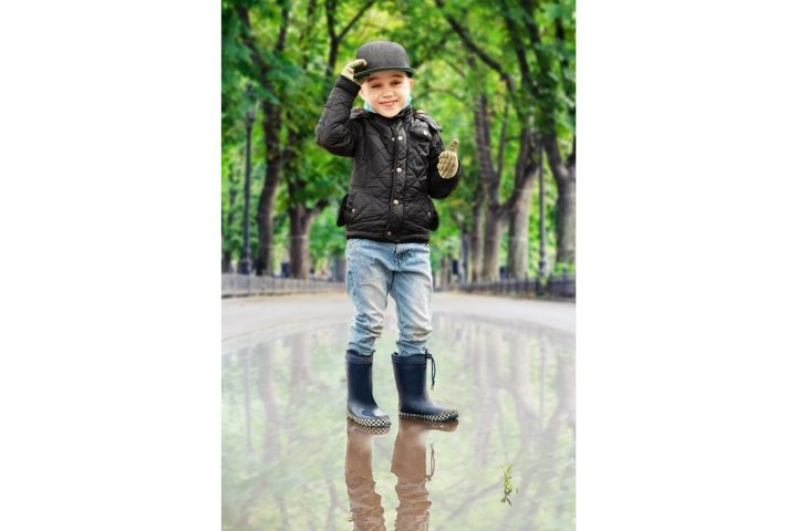 Happy smiling boy showing thumbs up gesture outdoors