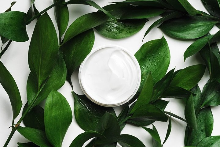White cream in open jar with green tropical foliage