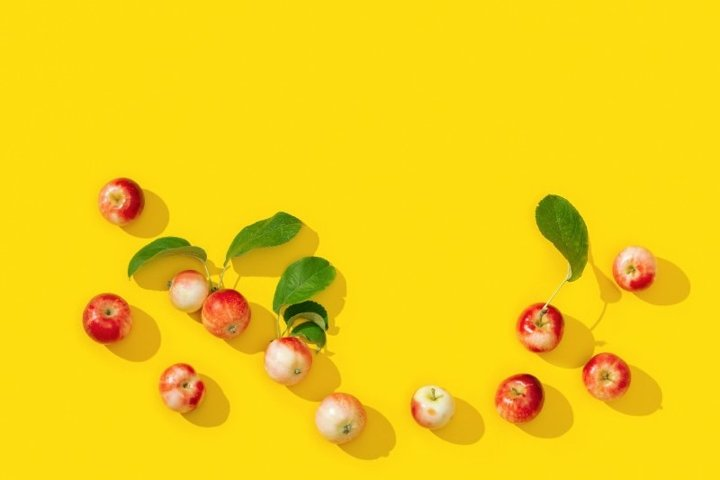 Small red apples frame on yellow background