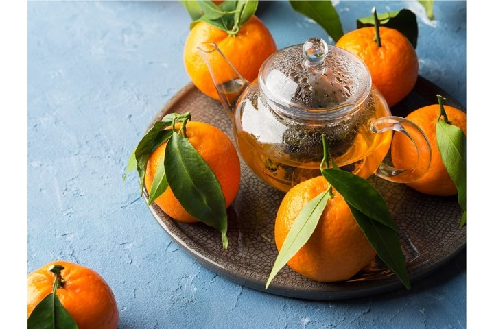 Winter tea in pot and tangerines on blue backgound