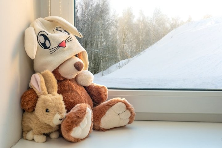 Teddy bear and bunny sits on window still. Winter, christmas